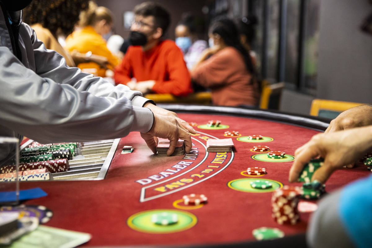 Student Chuong Van shuffles cards while working a blackjack table during class at the Crescent ...