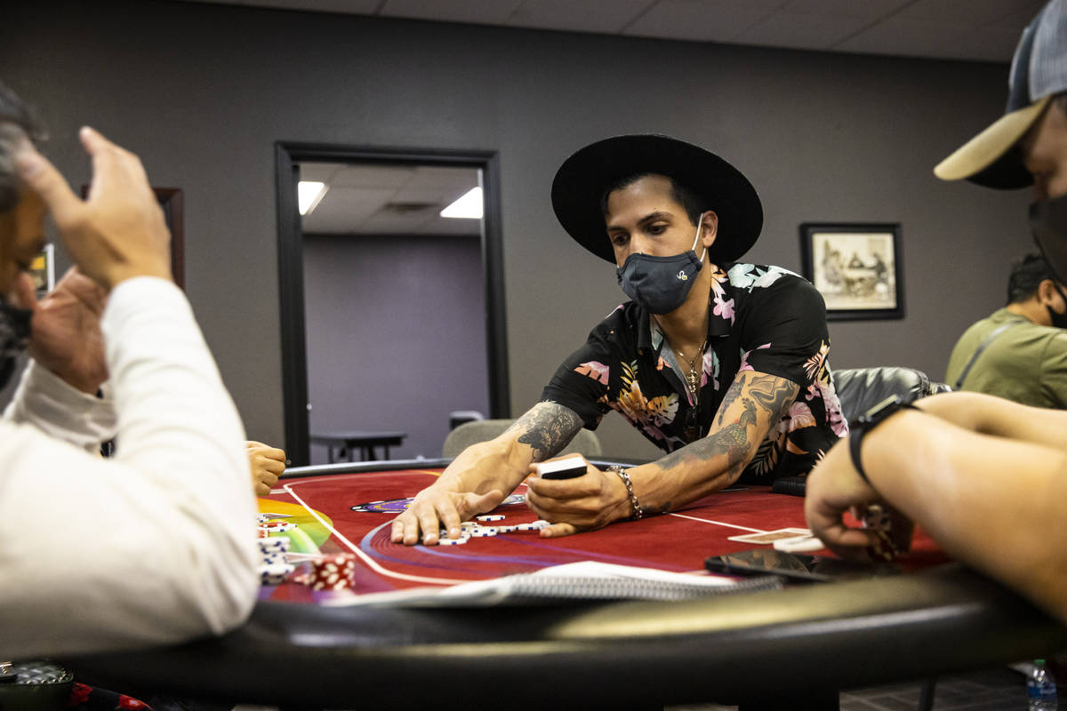 Student Christopher Montenegro, right, collects chips while working a poker table during class ...