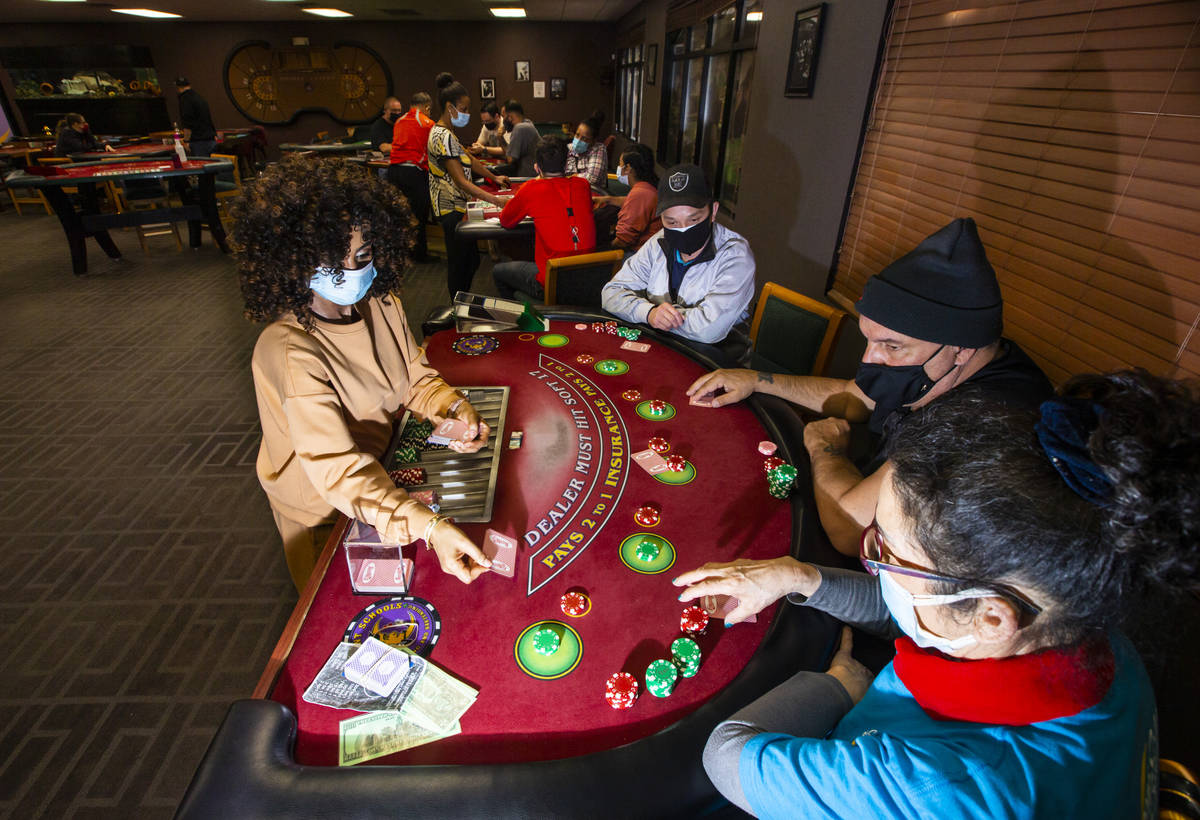 Instructor Yodit Girma, left, deals cards while working a blackjack table with students, from l ...