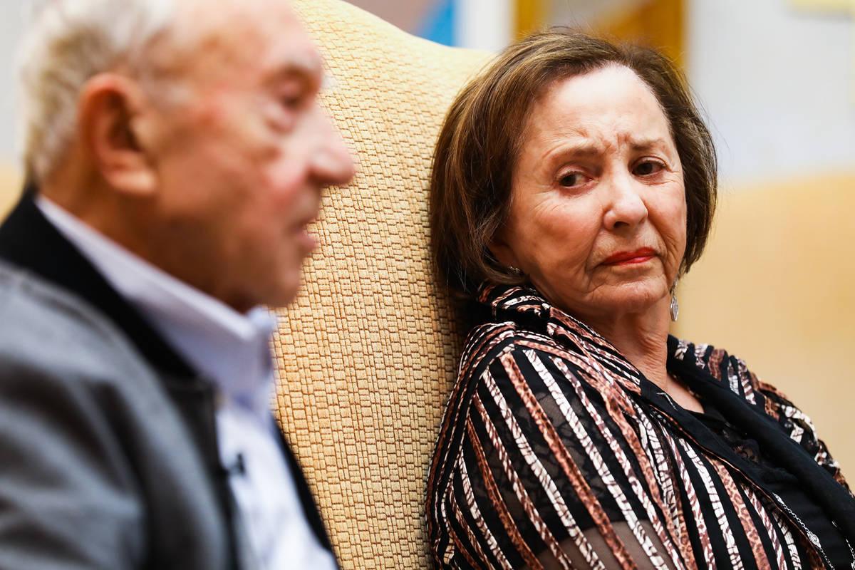 Holocaust survivor Judy Mack listens as fellow survivor Henry Kronberg speaks about his experie ...