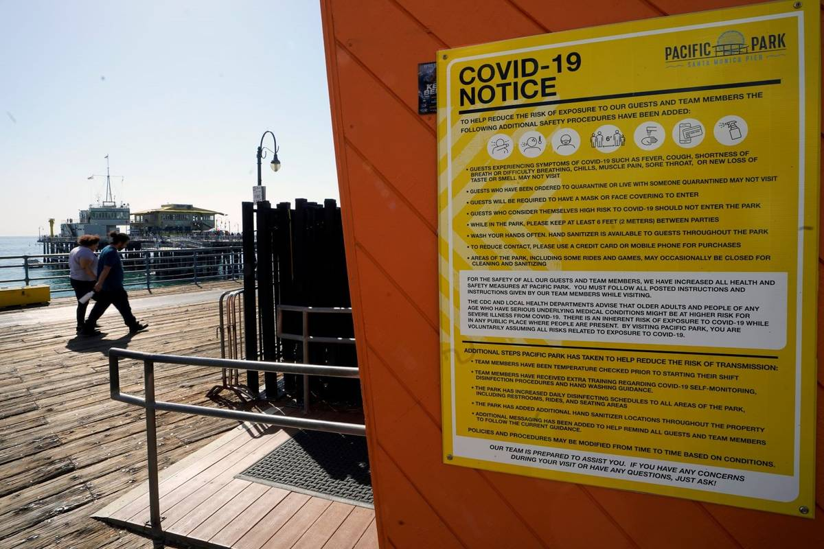 A COVID-19 notice is posted on the closed Pacific Park in the Santa Monica Pier in Santa Monica ...