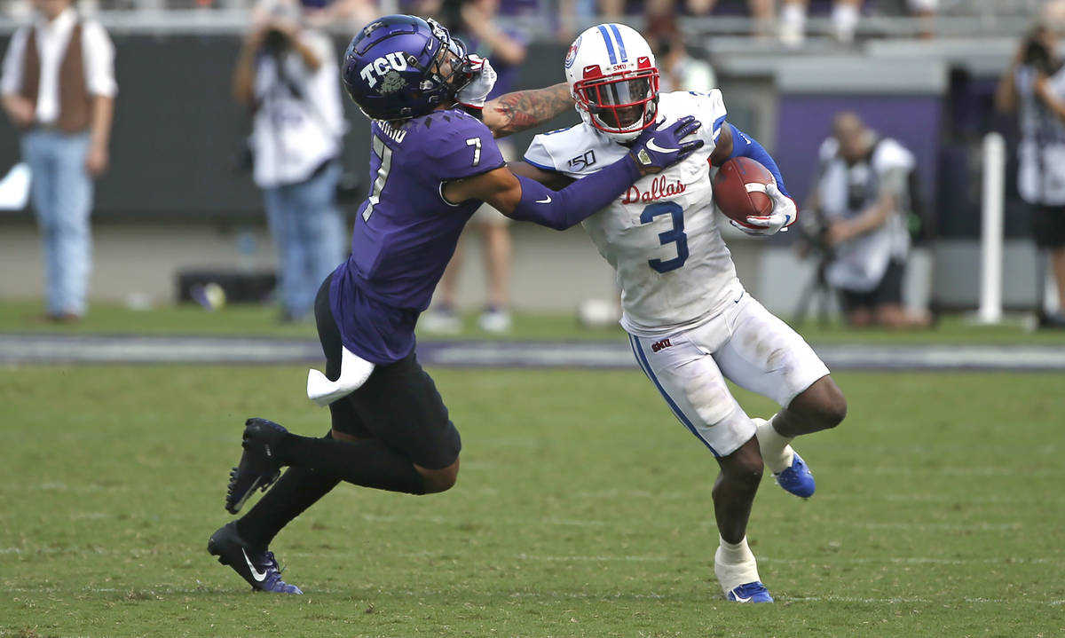 TCU safety Trevon Moehrig (7) pushes SMU wide receiver James Proche (3) toward the sideline aft ...