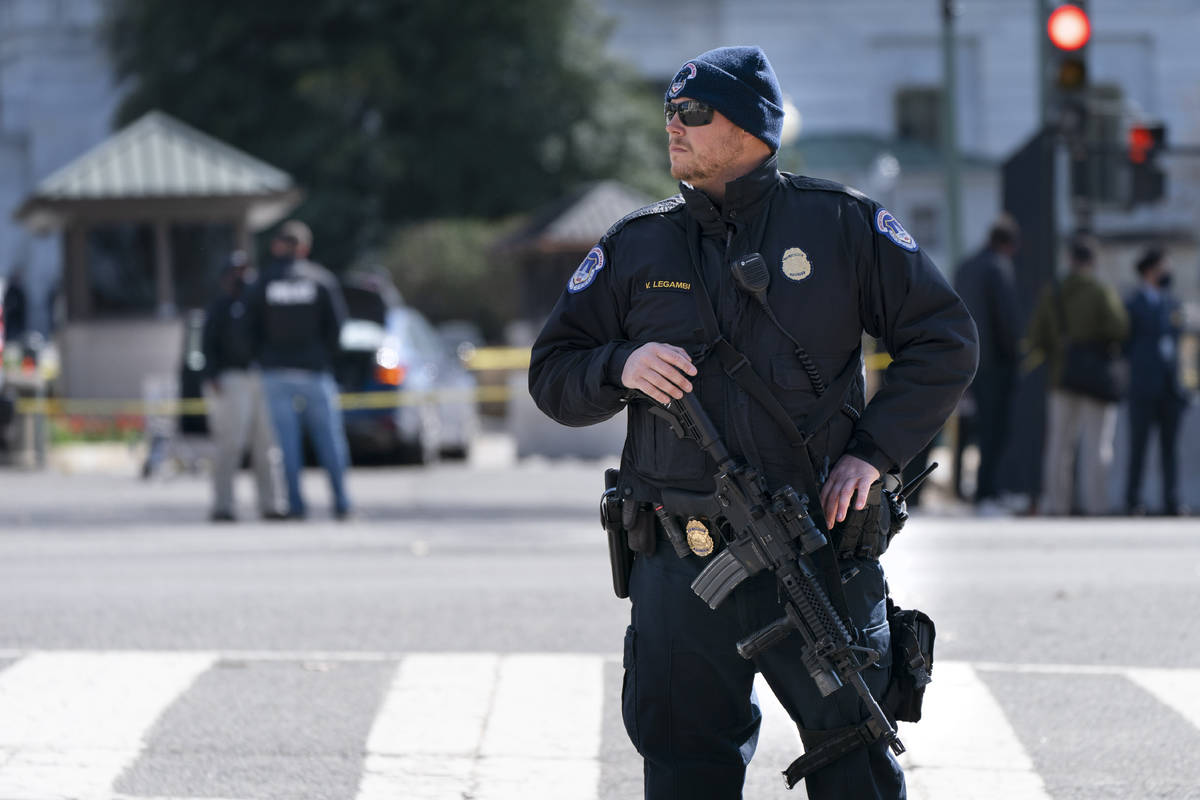 A Capitol Police officer patrols with a rifle at the site where a car crashed into a barrier on ...