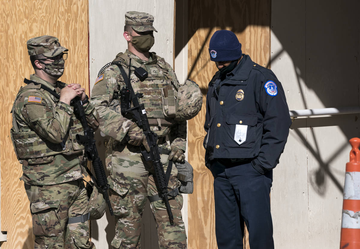 A U.S. Capitol Police officer, right, stands with two National Guard members near the scene whe ...