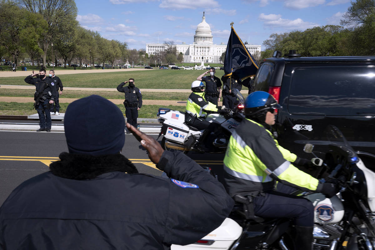 With the U.S. Capitol in the background, U.S. Capitol Police officers salute as procession carr ...