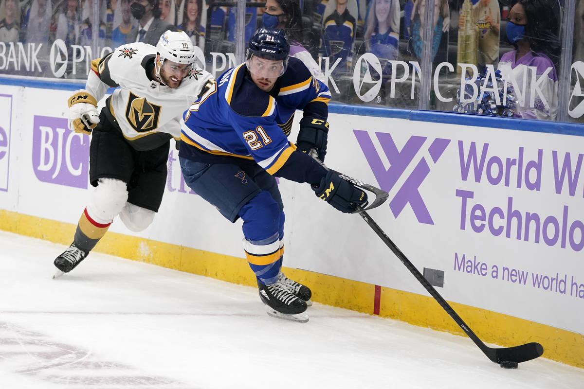 St. Louis Blues' Tyler Bozak (21) controls the puck as Vegas Golden Knights' Nicolas Roy (10) d ...