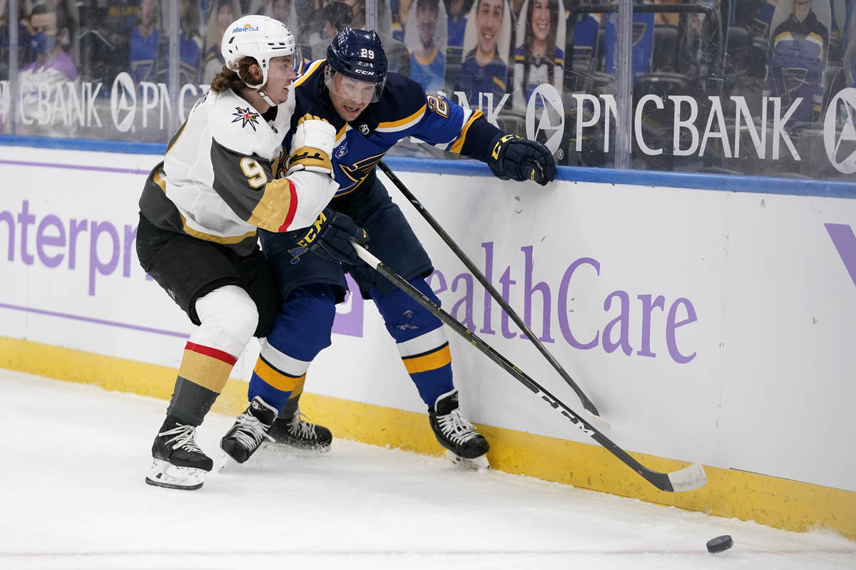 St. Louis Blues' Vince Dunn (29) and Vegas Golden Knights' Cody Glass (9) chase after a loose p ...