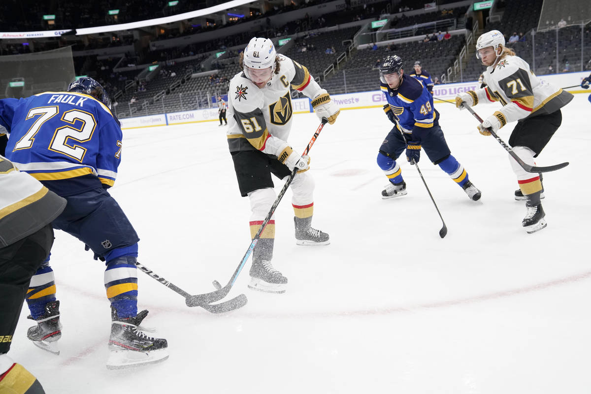 Vegas Golden Knights' Mark Stone (61) and St. Louis Blues' Justin Faulk (72) reach for a loose ...