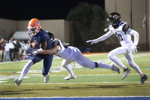 Bishop Gorman's Jonathan Brady (6) runs the ball for a touchdown under pressure from Faith Luth ...
