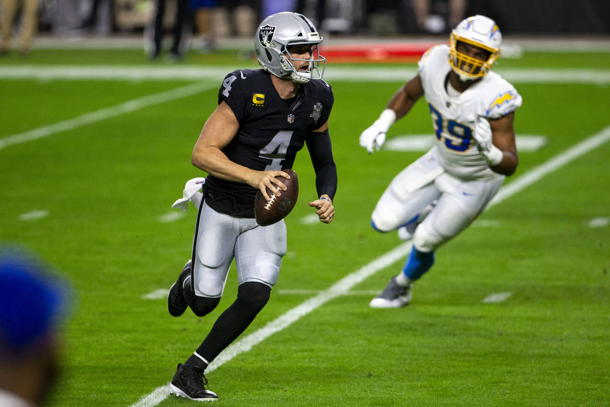 Raiders quarterback Derek Carr (4) scrambles with the football as Los Angeles Chargers cornerba ...