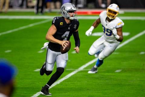 Raiders quarterback Derek Carr (4) scrambles with the football as Los Angeles Chargers cornerba ...