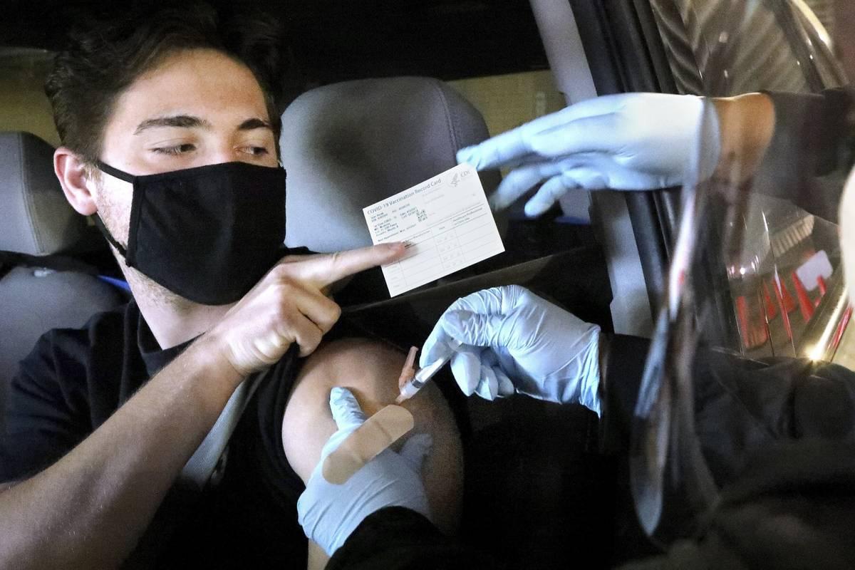 Tyler Rorah, 18, of Brooksville, receives a Moderna COVID 19 vaccine shot from LPN Sonie Woods, ...