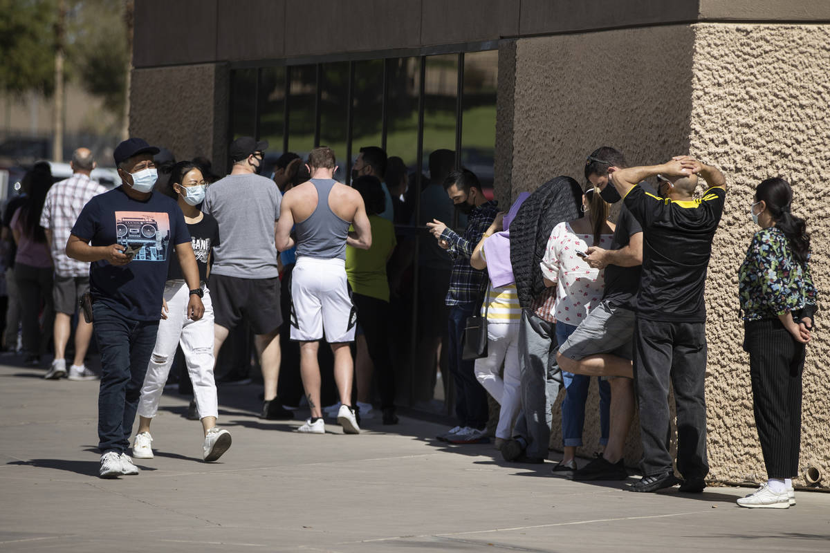 People wait in line to receive the COVID-19 vaccine at the Cashman Center in Las Vegas, Tuesday ...