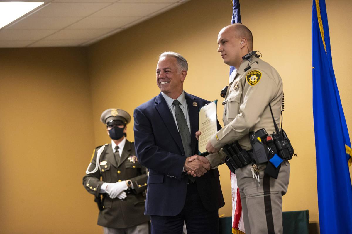 Sheriff Joe Lombardo presents police officer Jovan Magazin with an award for lifesaving efforts ...
