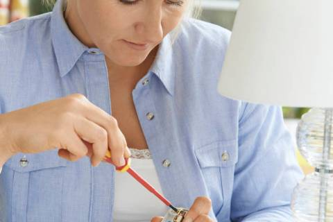 A woman wires an electrical plug on a lamp. (Getty Images)