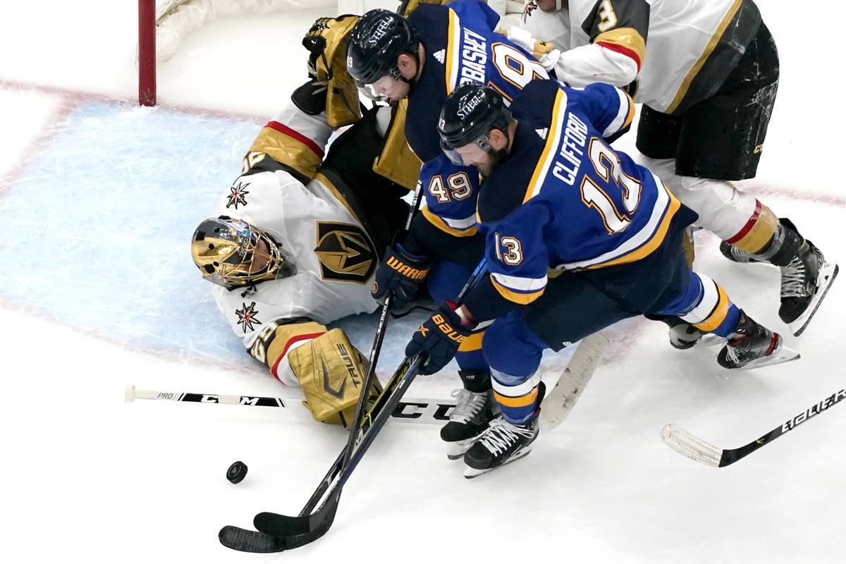 Vegas Golden Knights goaltender Marc-Andre Fleury, left, reaches for a puck along with St. Loui ...