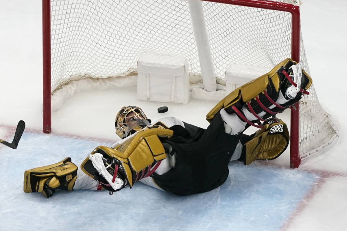 Vegas Golden Knights goaltender Marc-Andre Fleury slips as a puck flies by during the third per ...