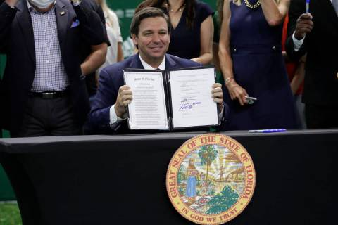 Florida Gov. Ron DeSantis holds up a signed bill which would allow college athletes in the stat ...