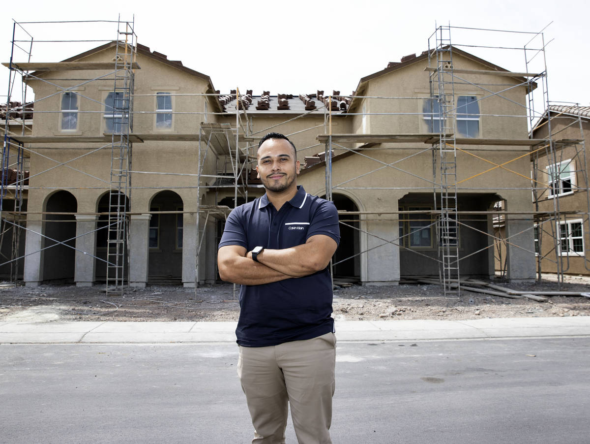 Gustavo Lopez, a realtor at Scofield Realty, poses for a photo in front of a new housing commun ...