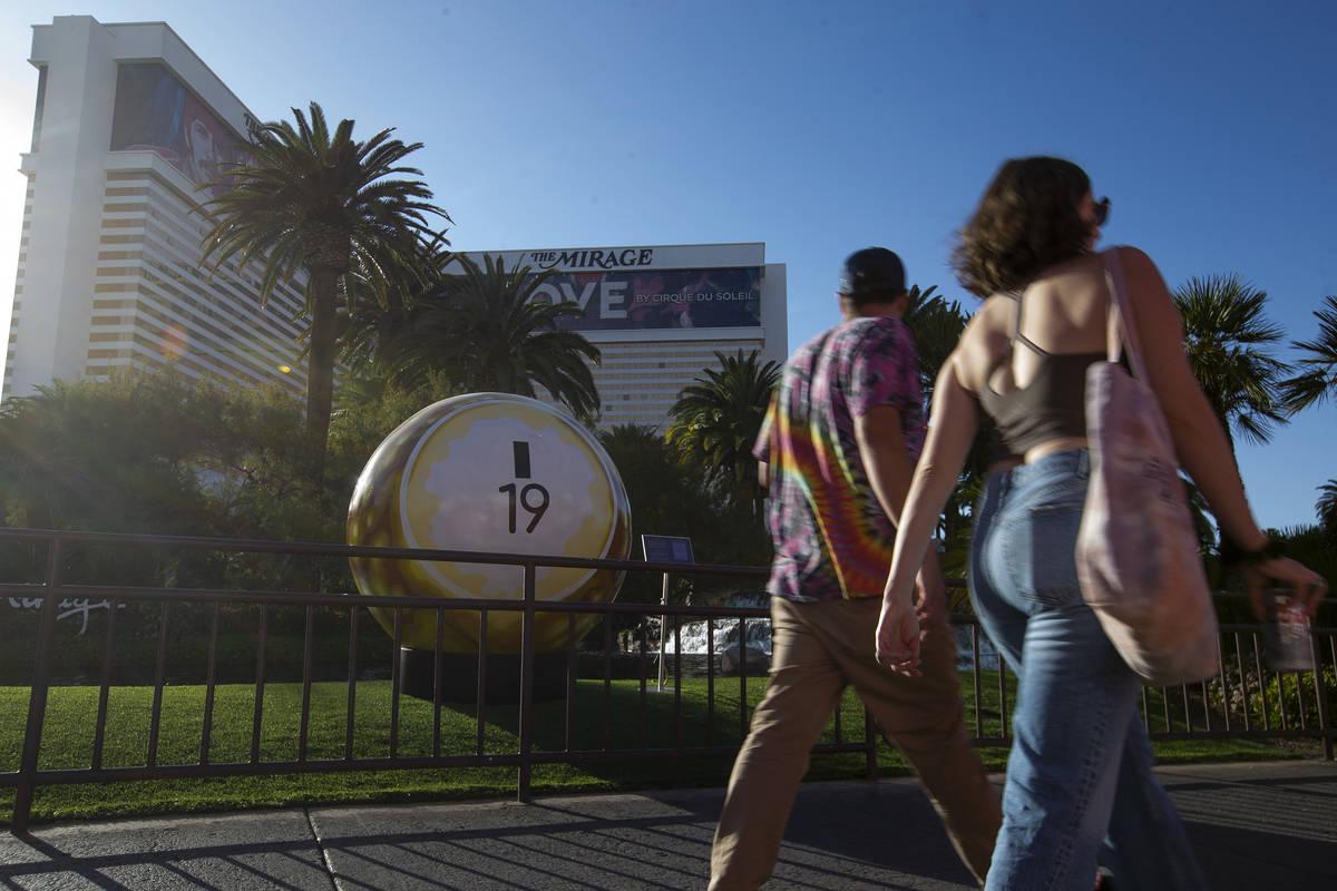 Pedestrians pass a 200-pound bingo ball by artist Jerry Misko, displayed in front of The Mirage ...