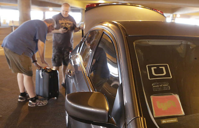 Riders prepare to load their luggage into ride-hailing companies' Uber and Lyft car at McCarran ...