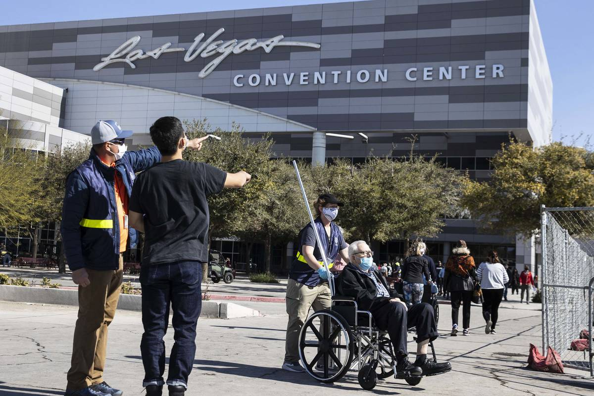 A FEMA employee directs people to the Las Vegas Convention Center's vaccine distribution area w ...