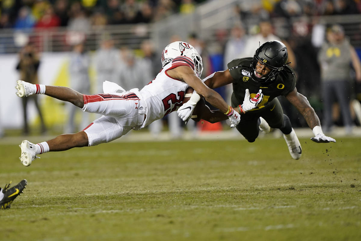 In this Dec. 6, 2018, file photo, Oregon safety Jevon Holland (8) breaks up a pass for Utah wid ...