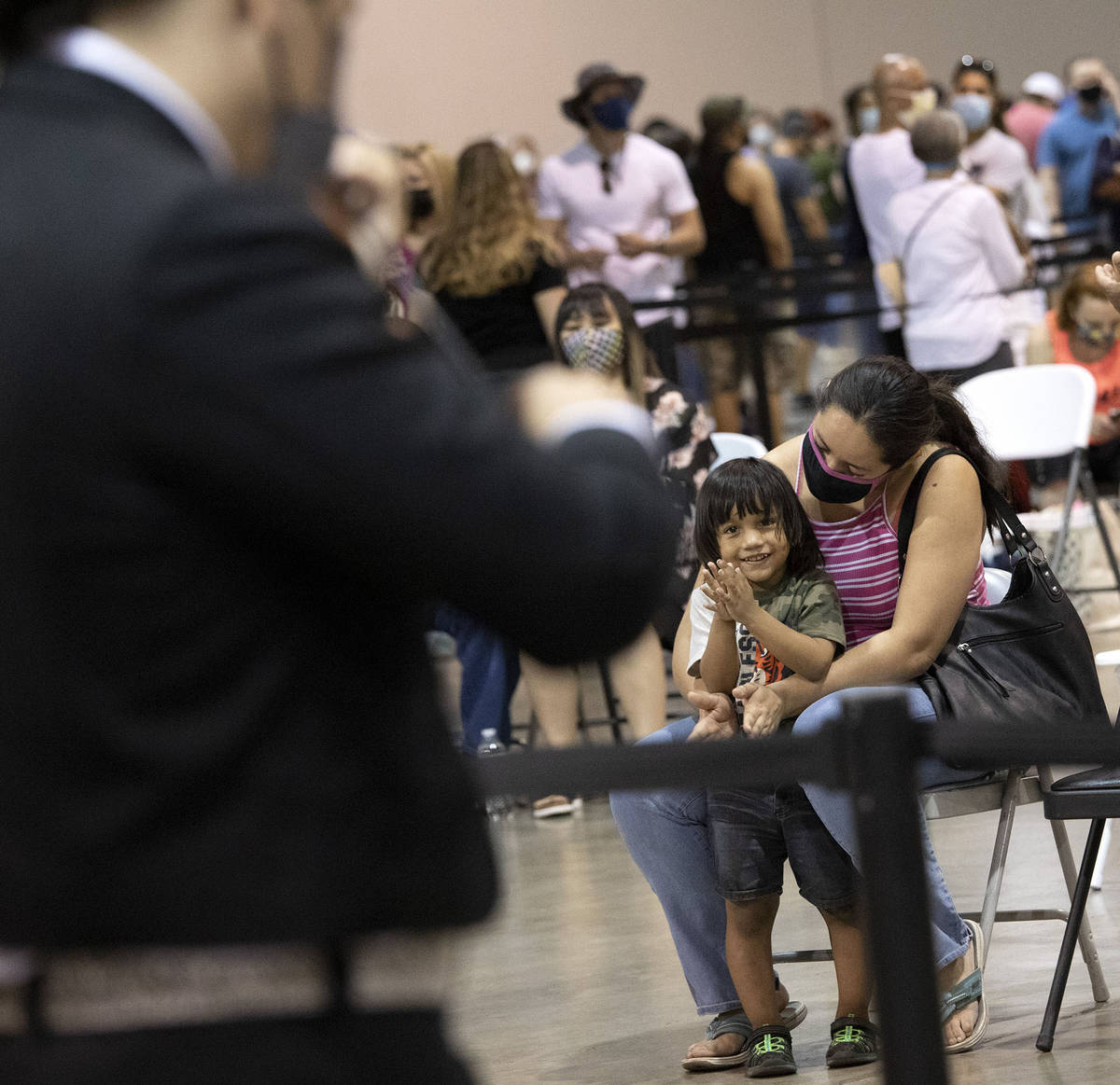 Elizabeth Montanez holds her son, Juan Mejia, 2, as he claps for Mariachi Nuestras Raices' perf ...