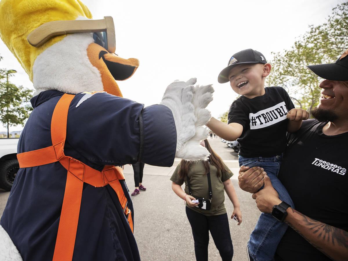 Las Vegas Aviators mascot Spruce the Goose, left, high-fives Jessie Yanez, 4, during a vehicle ...