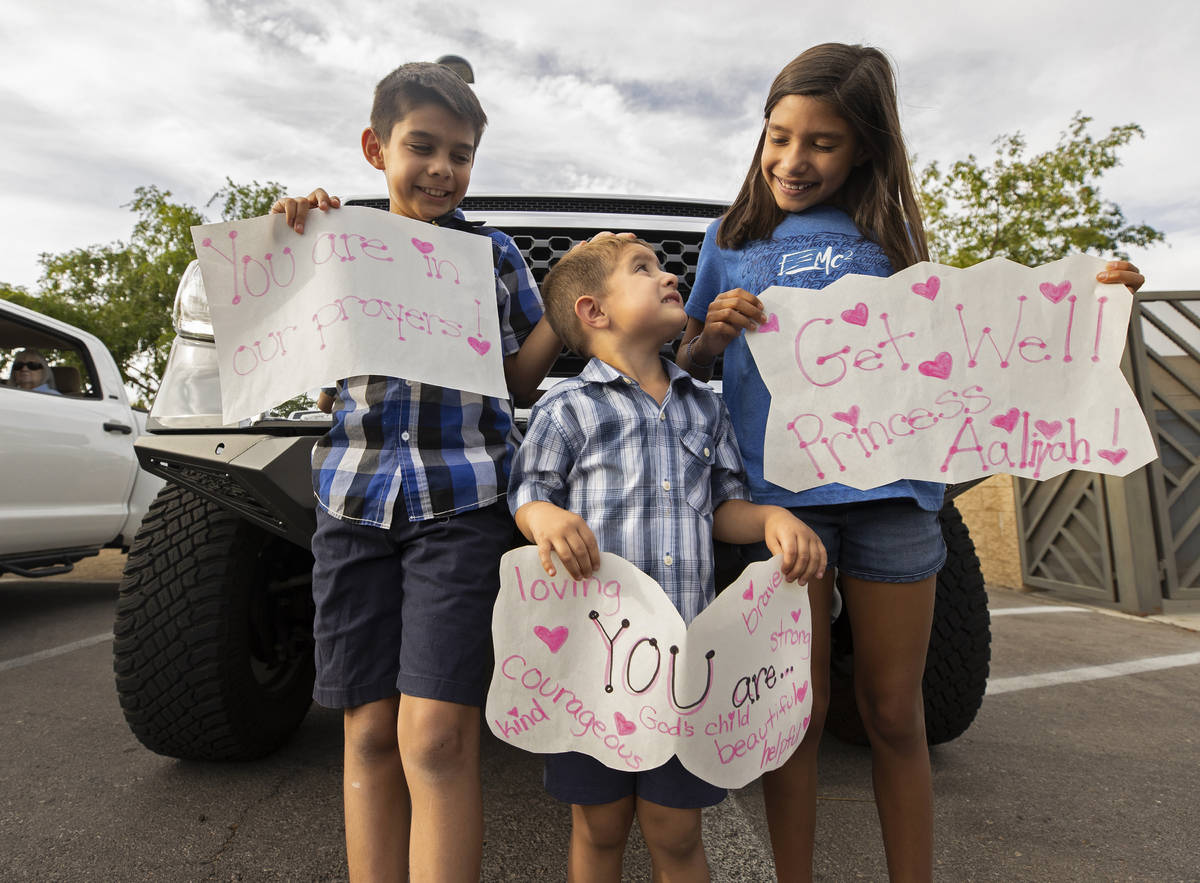 Asher, 9, Angelo, 3, and Arabella, 9, hold signs to support 9-year-old Aaliyah Velasquez, who w ...