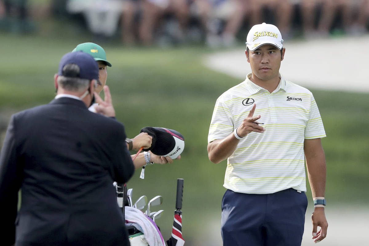 Hideki Matsuyama talks with a rules official after his ball went in the water on the fifteenth ...