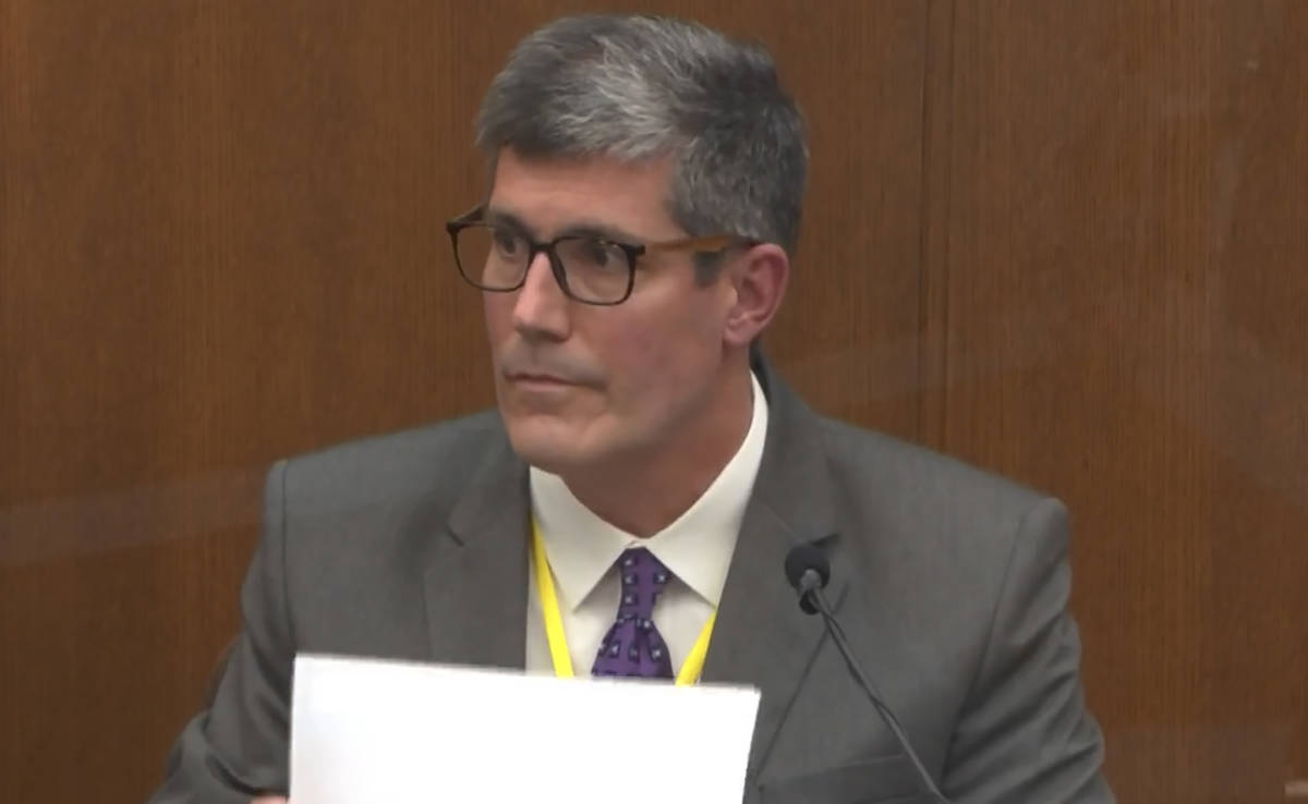 In this image from video, Dr. Andrew Baker, Hennepin County Medical Examiner, testifies as Henn ...