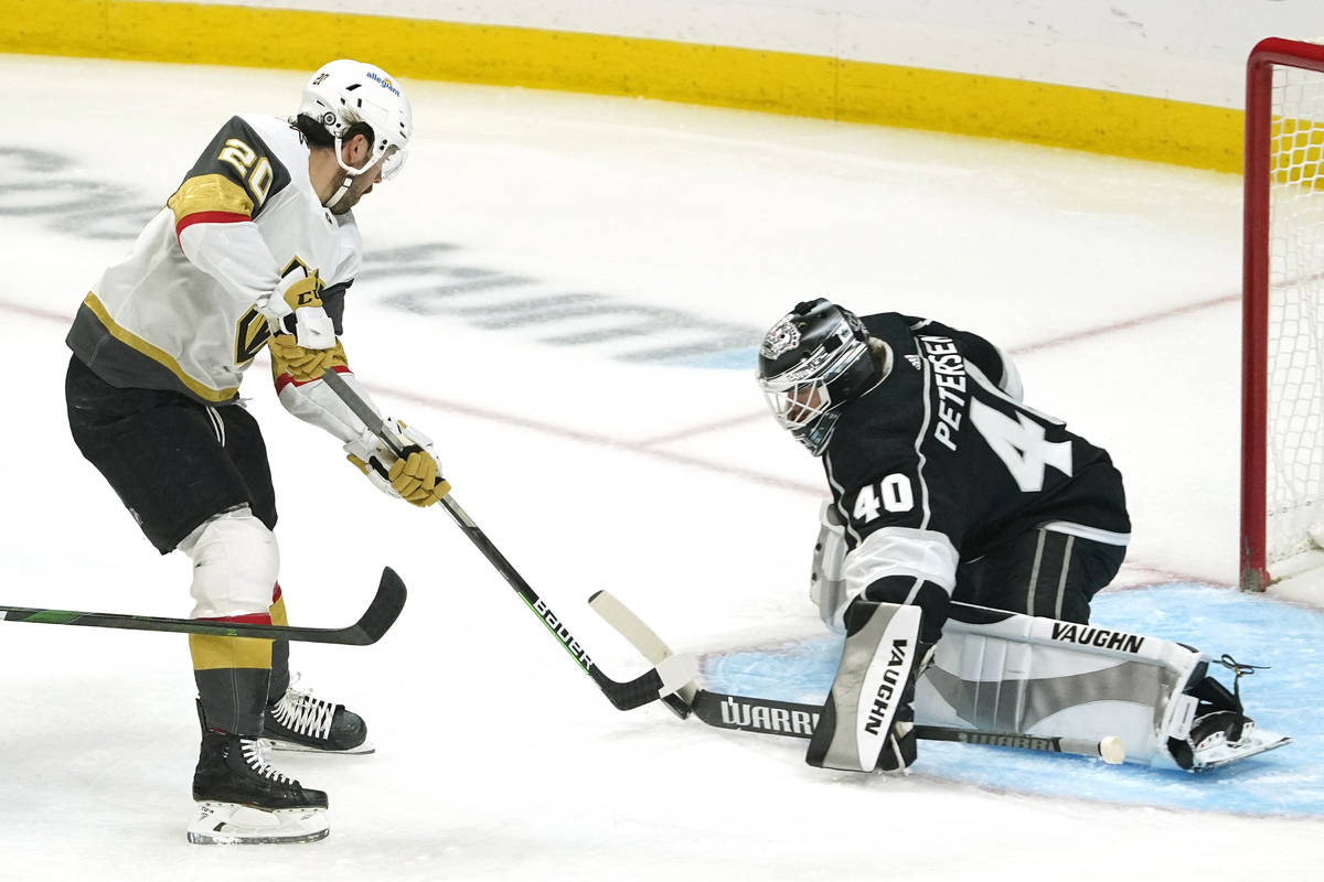 Vegas Golden Knights center Chandler Stephenson, left, tries to get a shot past Los Angeles Kin ...