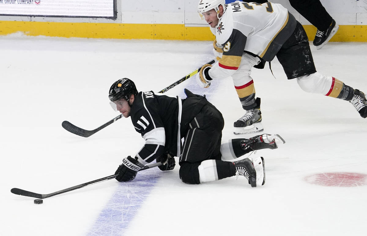 Los Angeles Kings center Anze Kopitar, left, trips while under pressure from Vegas Golden Knigh ...