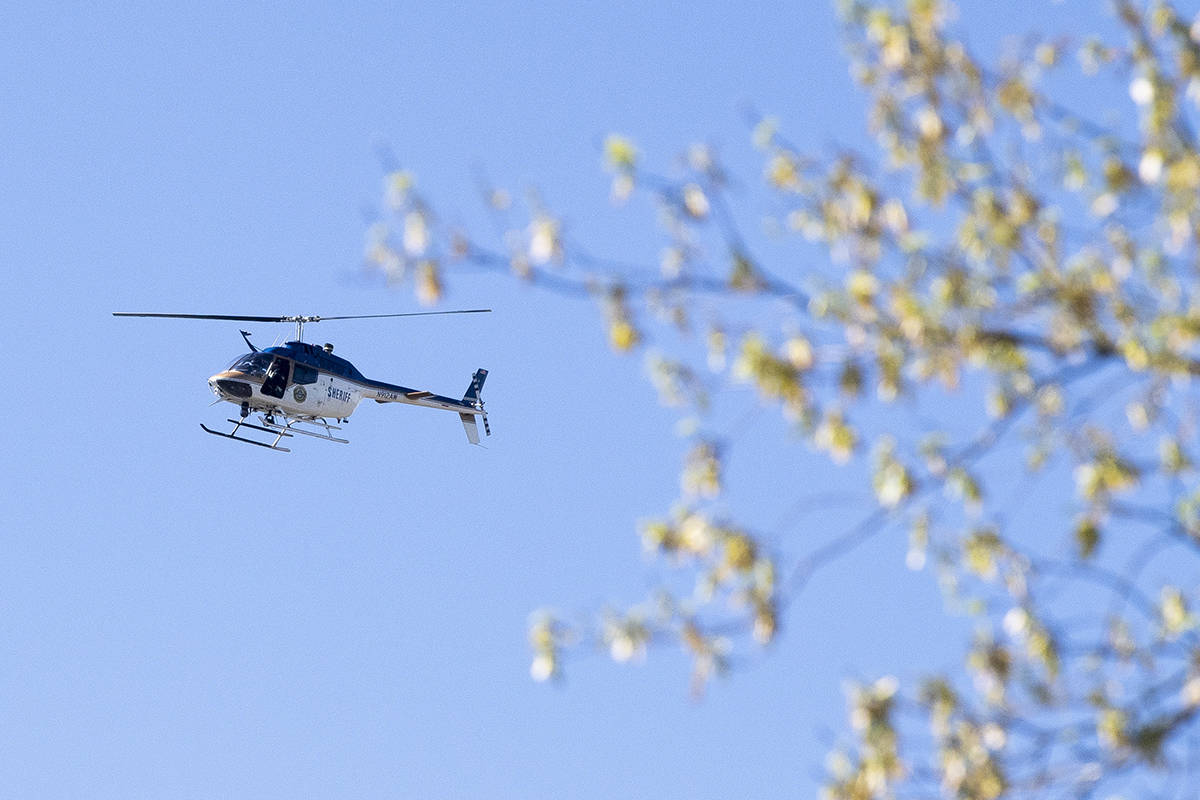 A law enforcement helicopter flies over the area of Austin-East Magnet High School after a repo ...