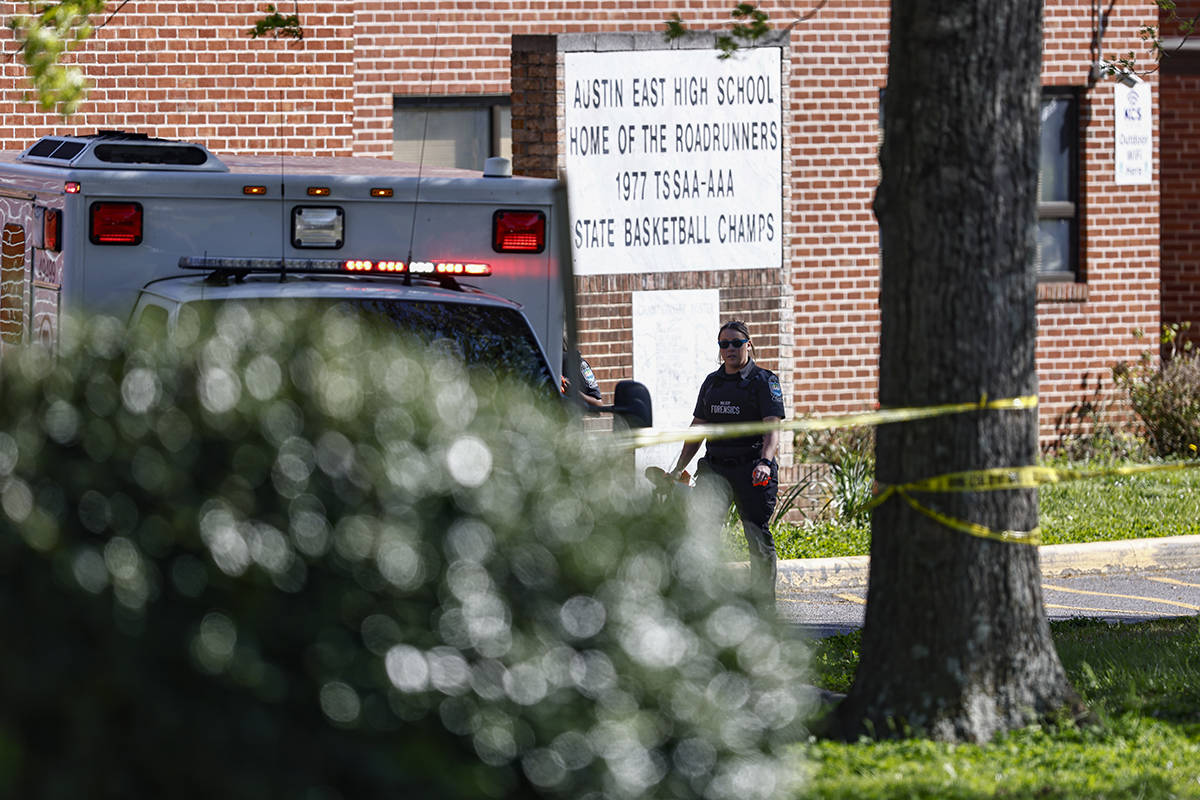 A member of the Knoxville police forensics team works the scene of a shooting at Austin-East Ma ...