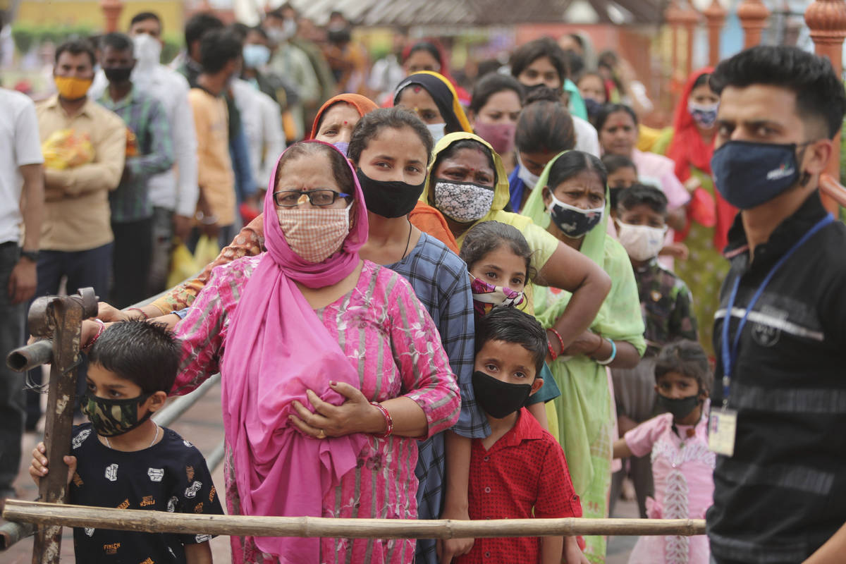 Hindu devotees wearing face masks as a precautionary measure against the coronavirus stand in a ...