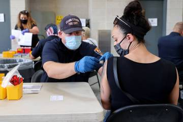 Clark County Fire Department Engineer Randy Cogburn gives a COVID-19 vaccine to Katye Burd, 30, ...