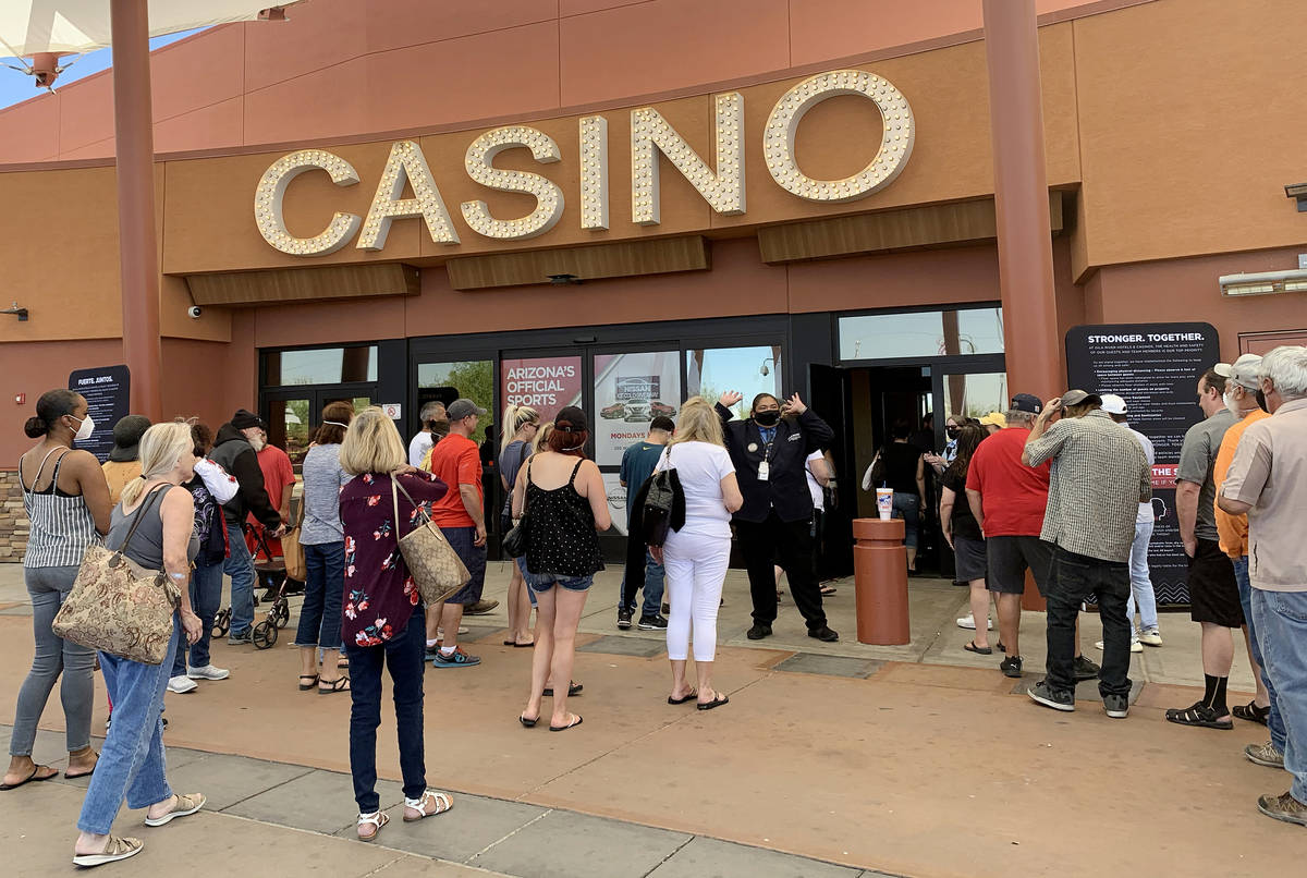 Players walk into Gila River Casino's Lone Butte location after waiting in line due to max capa ...