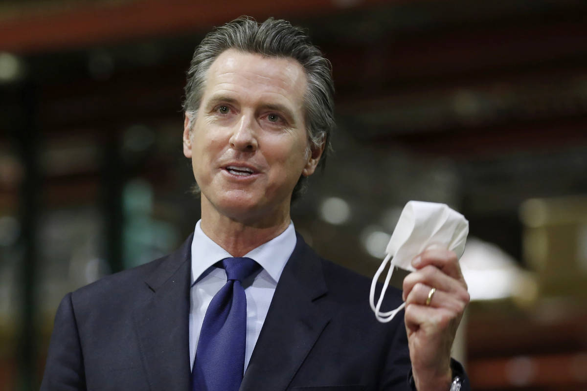 In this June 26, 2020, file photo, California Gov. Gavin Newsom holds a face mask during a news ...