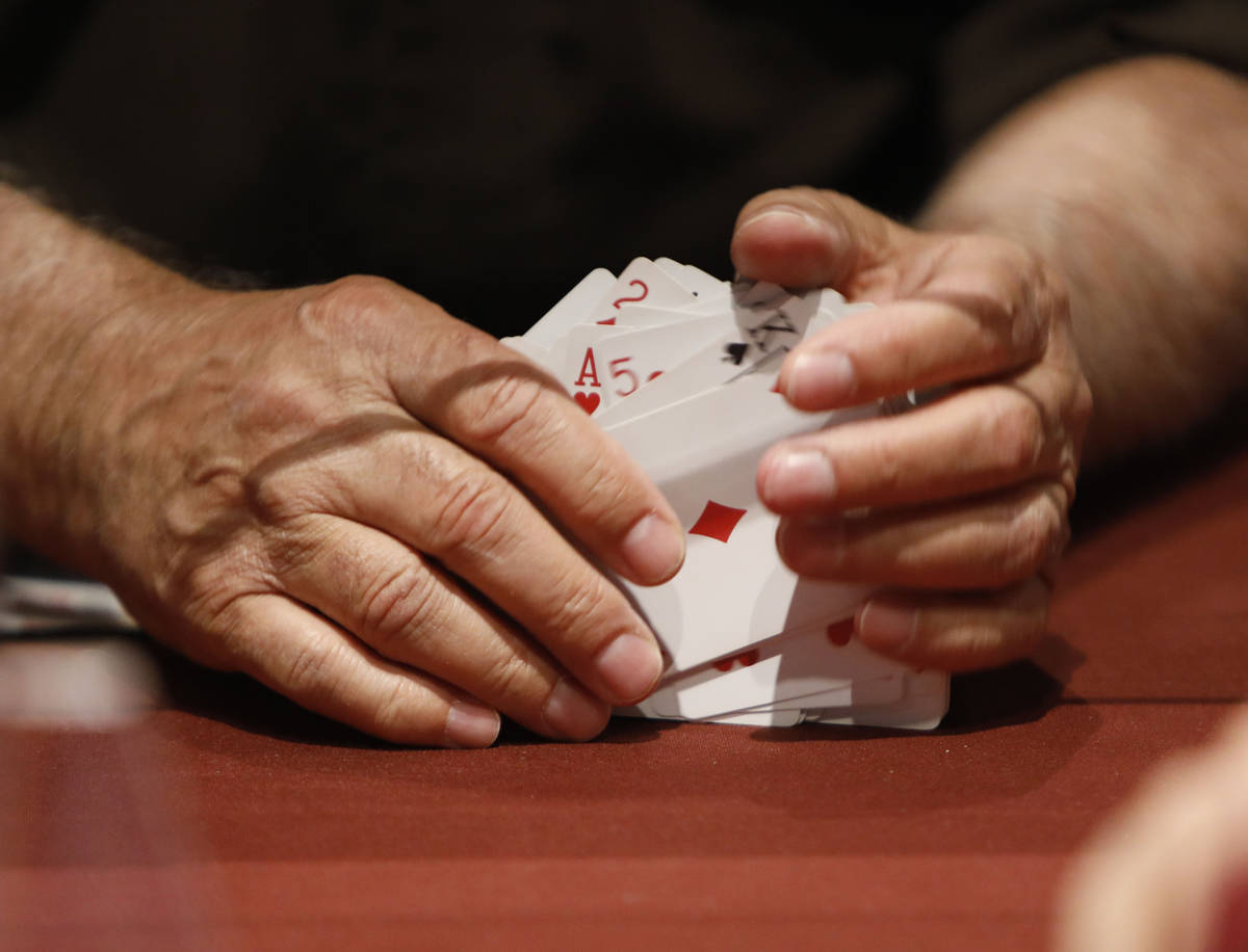 A dealer shuffles cards as women play in $175 No-Limit Hold'em Ladies tournament during 2021 Ne ...