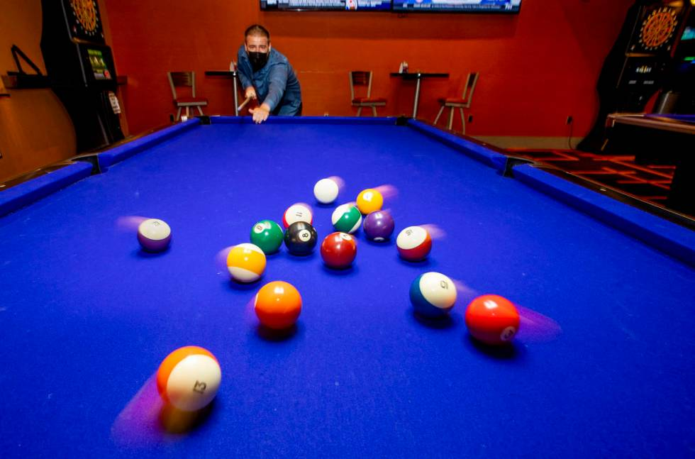 Joseph Turnell breaks the balls while playing pool at Red Rock Lanes, which has electronic dart ...