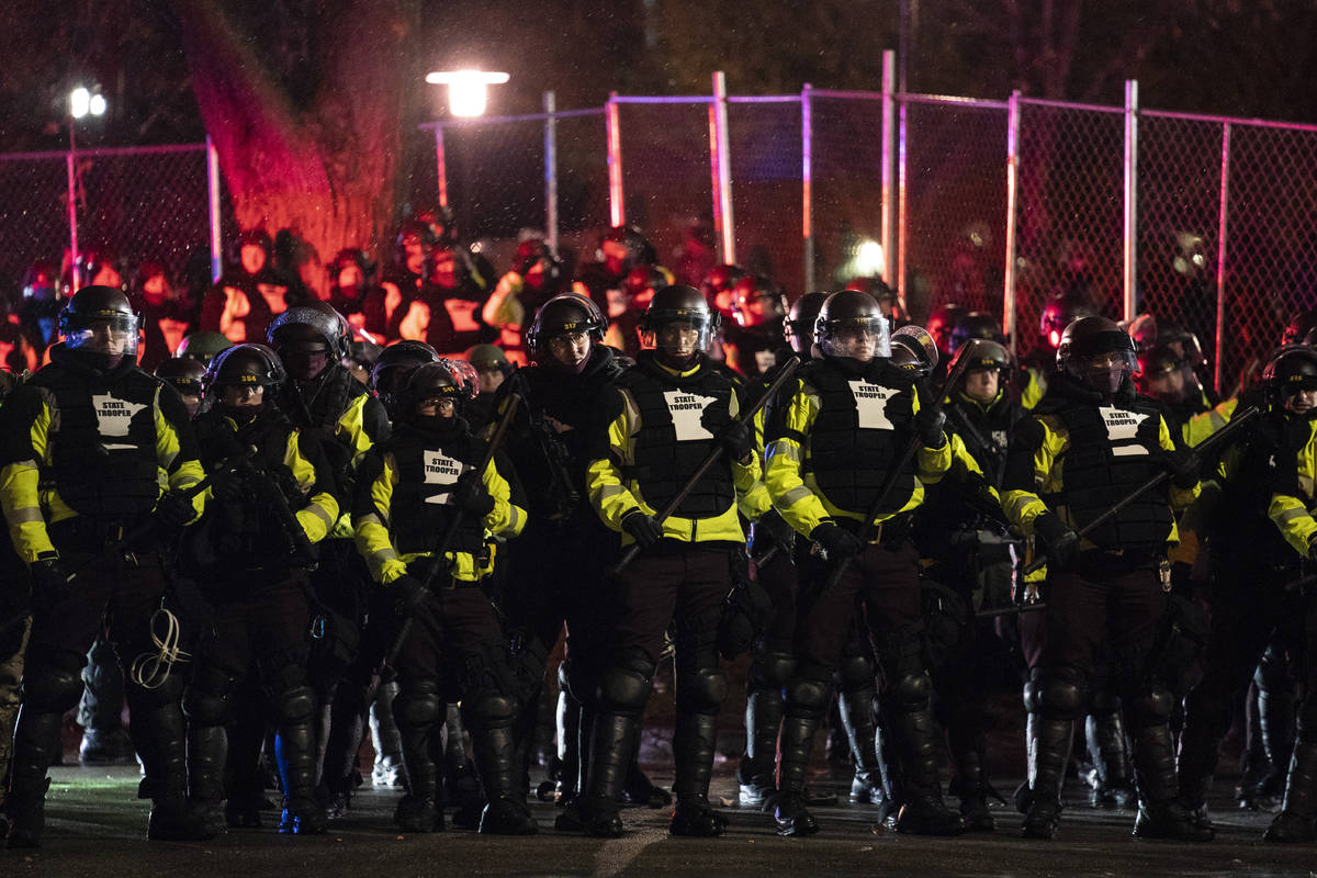 Authorities advance on demonstrators gathered outside the Brooklyn Center Police Department to ...