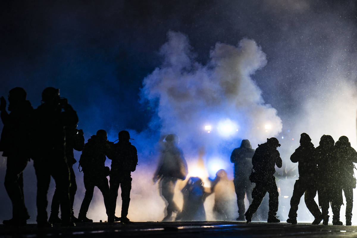Authorities fire gas munitions at demonstrators gathered outside the Brooklyn Center Police Dep ...