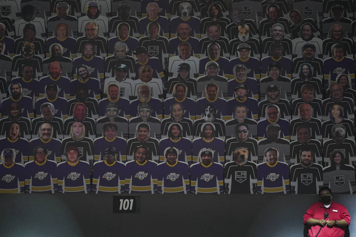 An usher stands next to a section of cutouts of fans in the stands at an NHL hockey game betwee ...