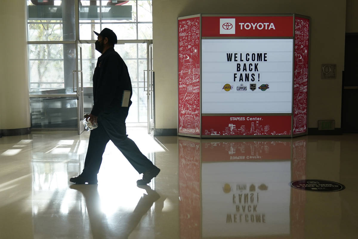 A man walks past a sign welcoming back fans before an NHL hockey game between the Vegas Golden ...