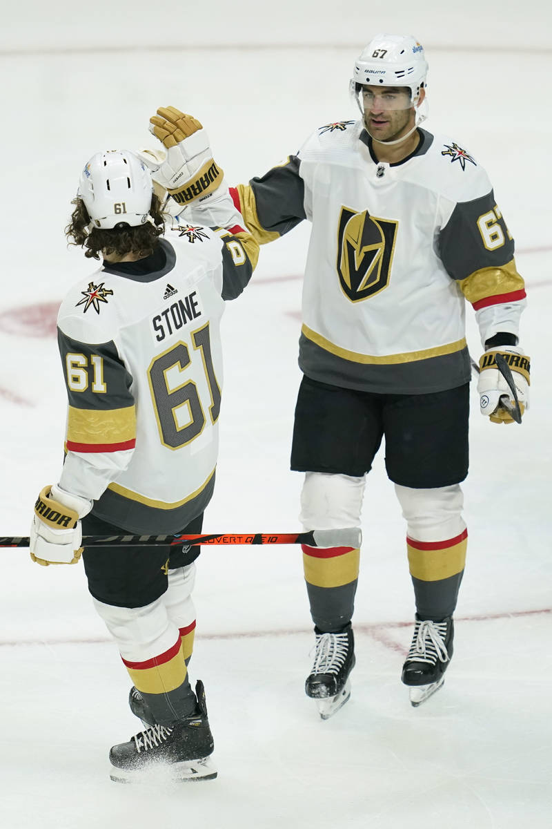 Vegas Golden Knights right wing Mark Stone (61) high-fives left wing Max Pacioretty (67) after ...