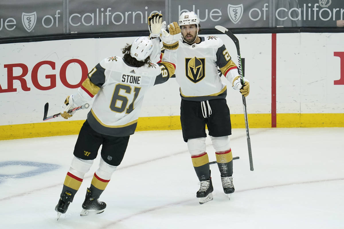 Vegas Golden Knights center Chandler Stephenson (20) high-fives right wing Mark Stone (61) afte ...