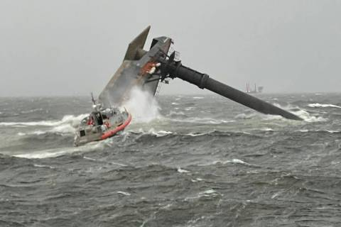 A Coast Guard Station Grand Isle 45-foot Respone Boat-Medium boatcrew heads toward a capsized 1 ...