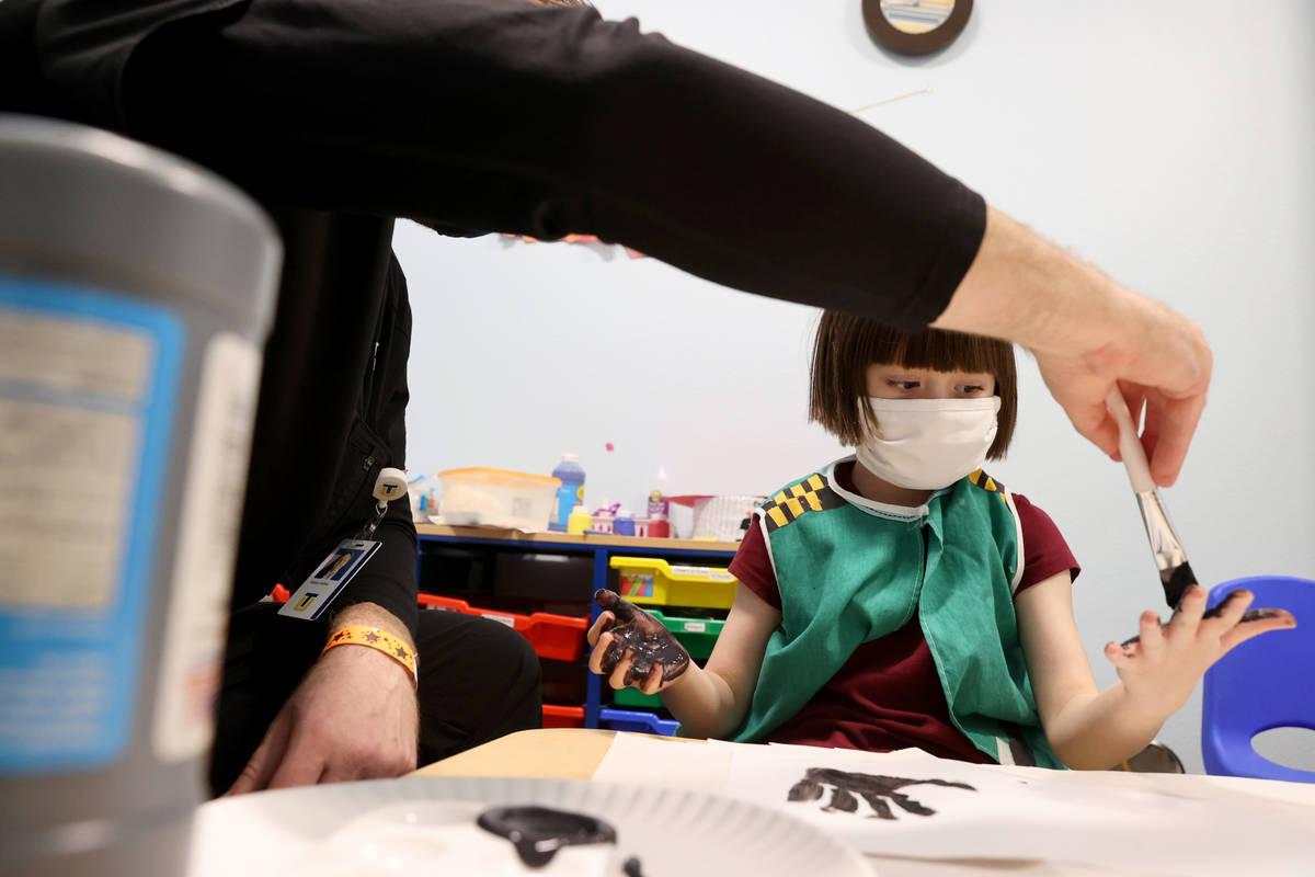 Akara Haase, 6, works with behavior analyst Adam Volker at the Center for Autism and Developmen ...